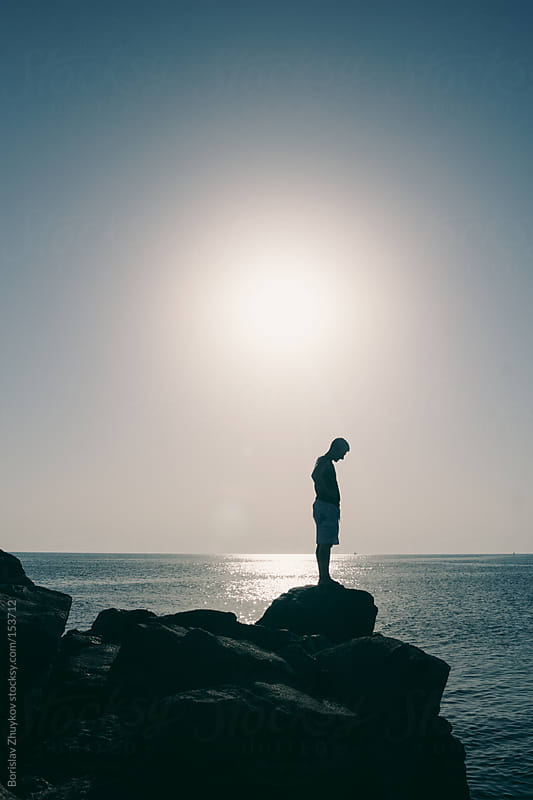 Summer male silhouette on a rock by the sea by Borislav Zhuykov for Stocksy United