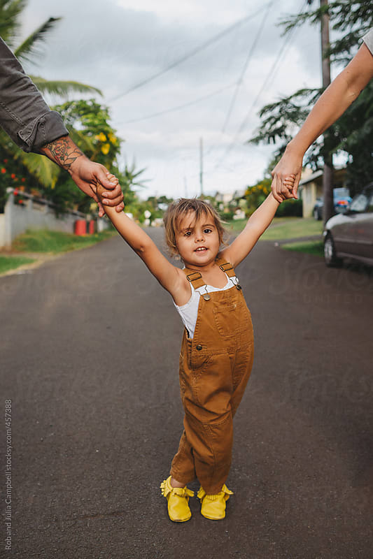 Cute young toddler girl standing on road at sunset holding parents hands by Rob and Julia Campbell for Stocksy United