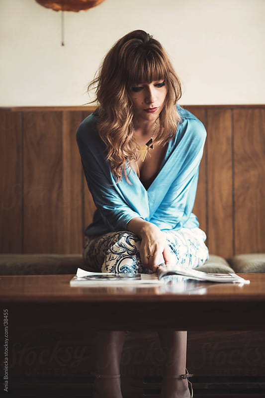 A beautiful stylish woman reading a magazine  by Ania Boniecka for Stocksy United