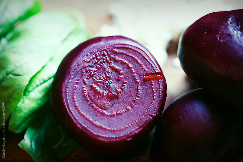 Close up of a sliced beet and basil by Carolyn Lagattuta for Stocksy United