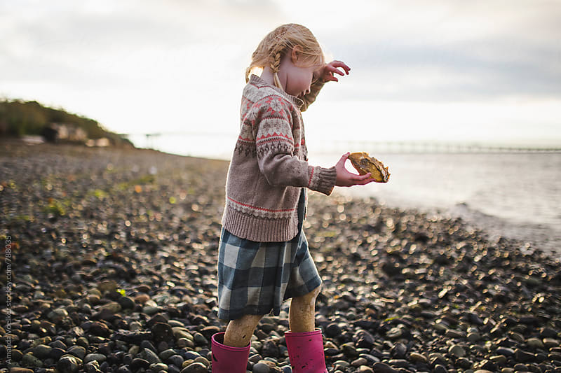 Little Girl Walks to the Shore Holding a Crab Shell by Amanda Voelker for Stocksy United