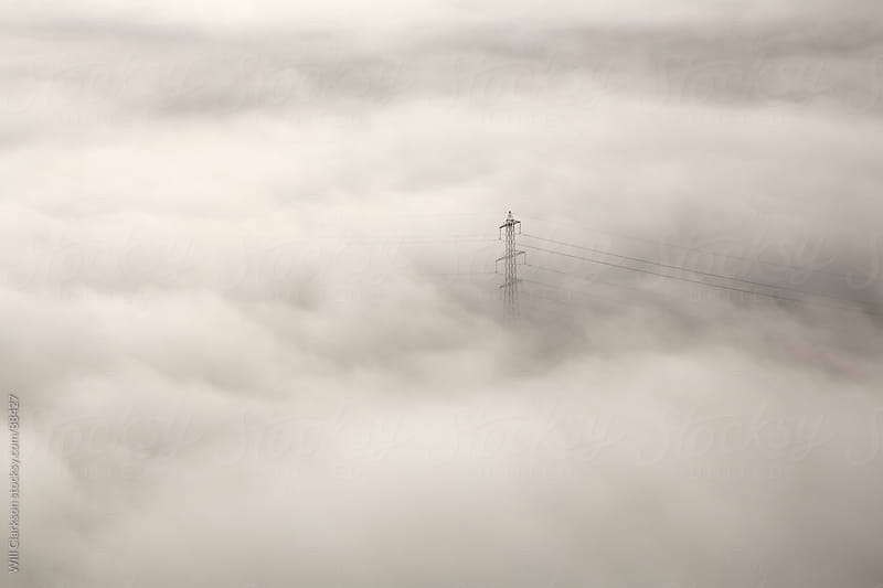 A pylon protrudes up above low clouds by Will Clarkson for Stocksy United