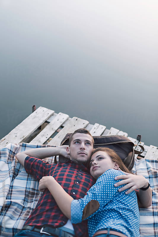 Couple resting by the lake by Dejan Ristovski for Stocksy United
