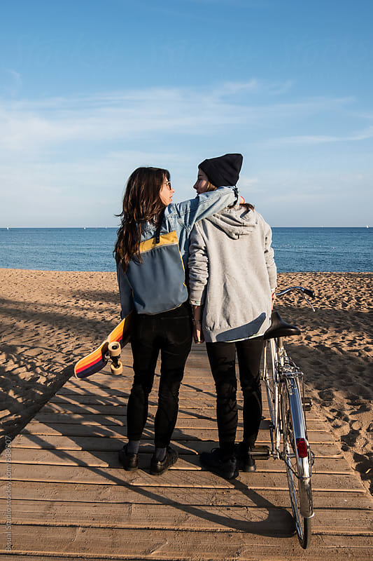 Two young women hanging out in Barcelona beach, Barcelona by Bisual Studio for Stocksy United