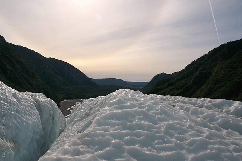 Icy landscape of the Franz Josef Glacier in New Zealand, lit by a halo-surrounded sun.  by Kaat Zoetekouw for Stocksy United