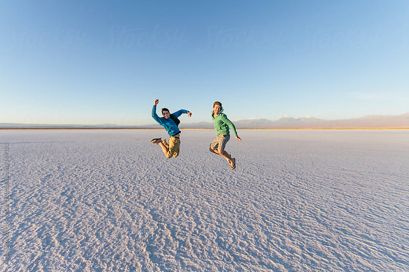 Two male friends jumping happy on salt flat desert landscape while adventure travel by Alejandro Moreno de Carlos for Stocksy United