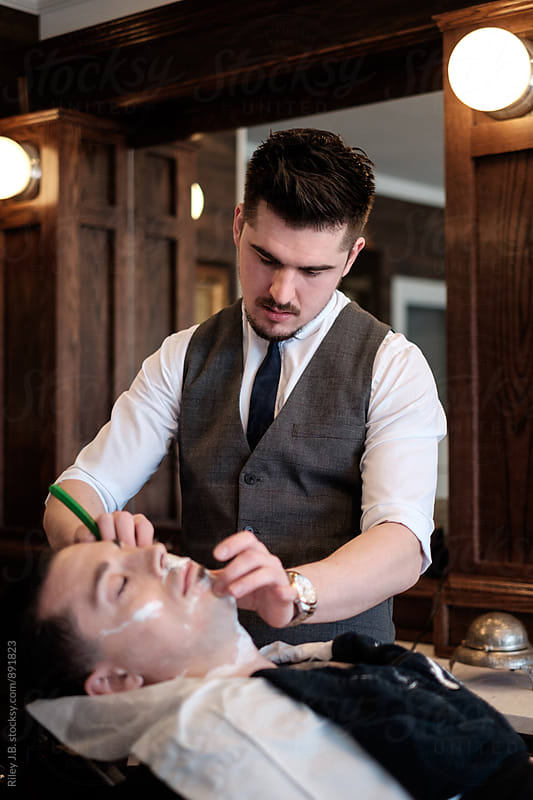 A young, dapper gentleman barber performing a classic straight razor shave on a client. by Riley J.B. for Stocksy United