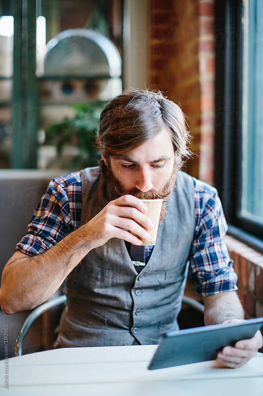 Fashionable man in a coffee shop by Jakob for Stocksy United