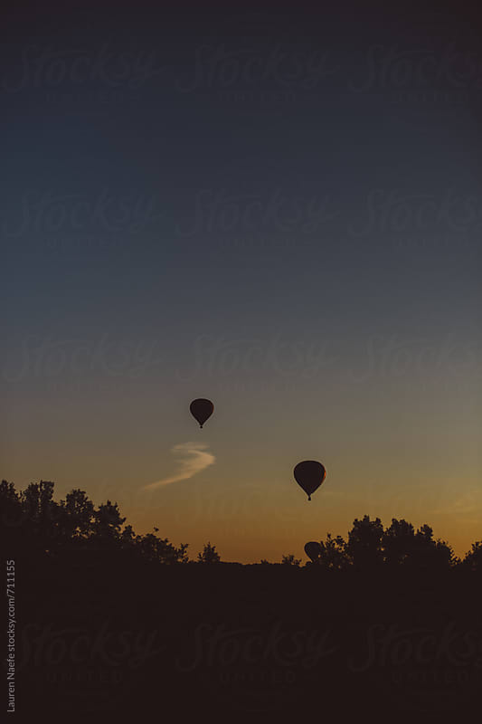 Two hot air balloon floating above the trees at dusk by Lauren Naefe for Stocksy United