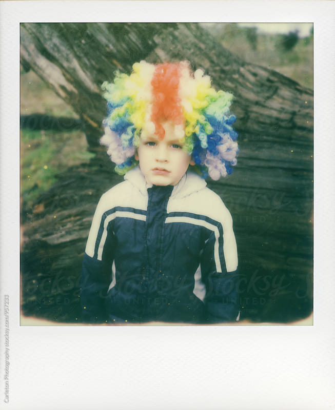 Four year old boy in jacket and rainbow clown wig isn't having it by Carleton Photography for Stocksy United