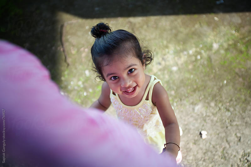 Cute little girl smiling,top view by Saptak Ganguly for Stocksy United