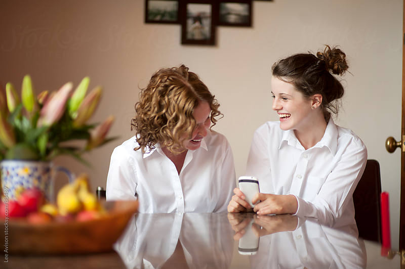 mother and daughter using a cell phone by Lee Avison for Stocksy United