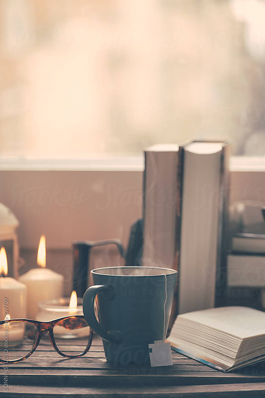Still life of used books, tea, glasses and candles on a wood table.  by BONNINSTUDIO for Stocksy United