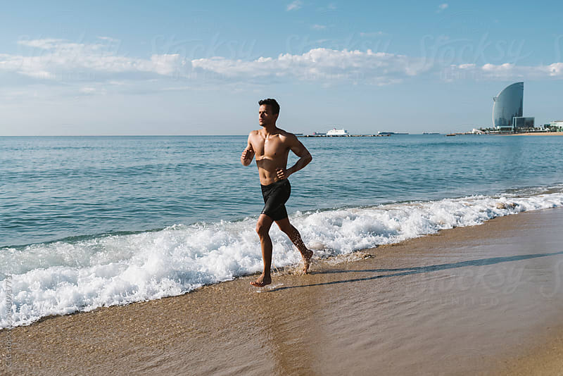Young Hispanic man running on the shore by Simone Becchetti for Stocksy United