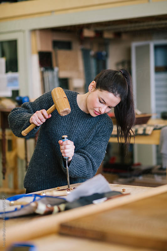 Female woodworker working on a bench , working with wooden hammer and chisel by Ivo de Bruijn for Stocksy United