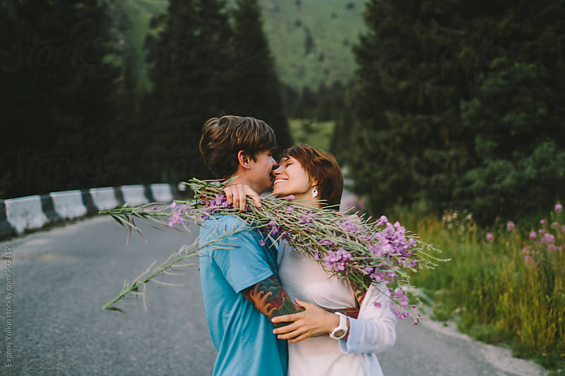 Young couple embracing on the mountain road by Evgenij Yulkin for Stocksy United