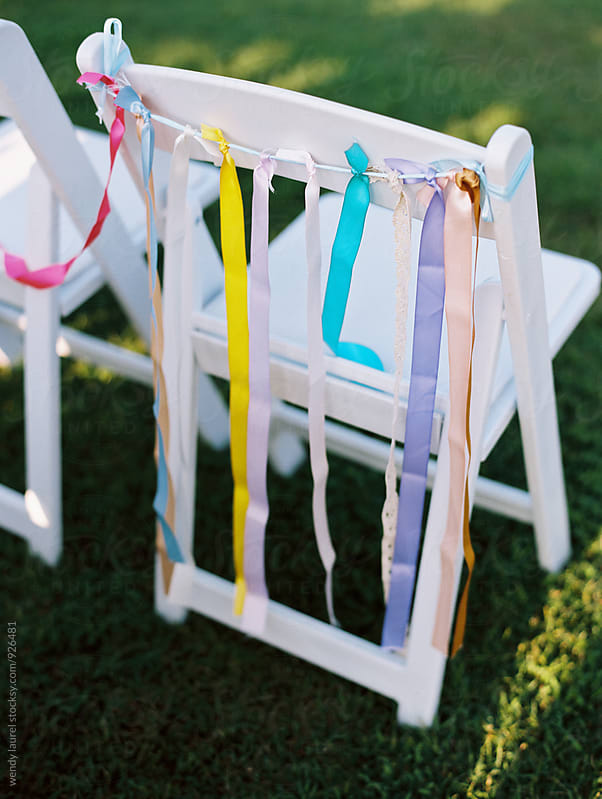 wedding chair decorated with rainbow colored ribbons by wendy laurel for Stocksy United