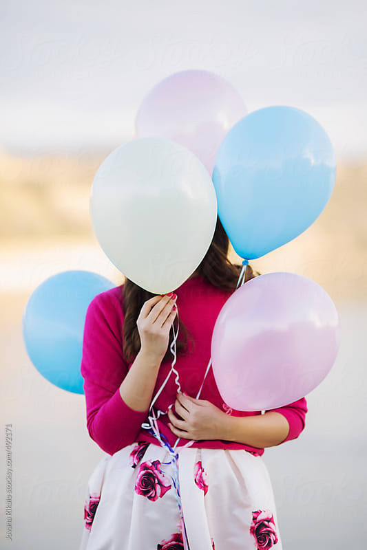 Young woman covering her face with balloons by Jovana Rikalo for Stocksy United