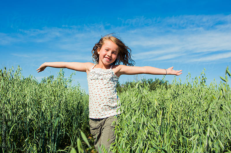 young girl running through grassy field by Tomas Kraus for Stocksy United
