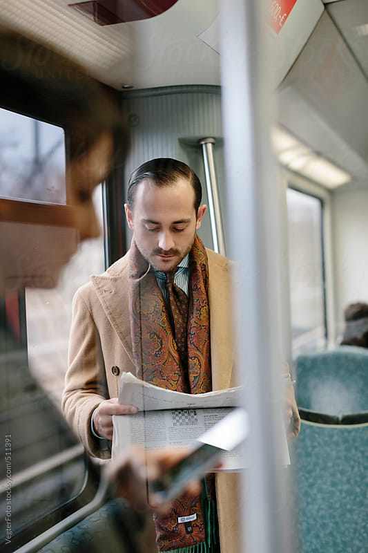 Reading Newspaper In Commuter Train by VegterFoto for Stocksy United