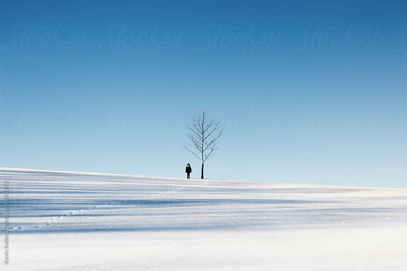 Young Boy Standing Near a Tree on a Sunny Winter Day by Kevin Keller for Stocksy United