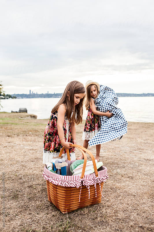 Twin sisters cleaning up after picnic in a park by Suprijono Suharjoto for Stocksy United