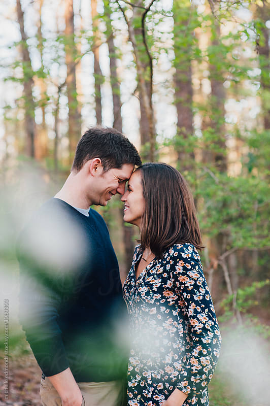 Couple Smiling Forehead to Forehead in the Woods by michelle edmonds for Stocksy United