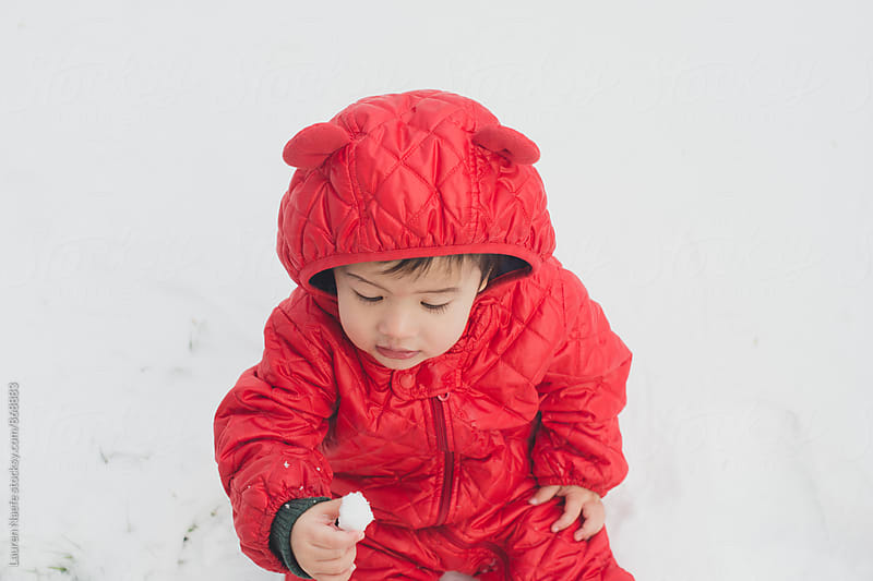 Baby looking at snow by Lauren Naefe for Stocksy United