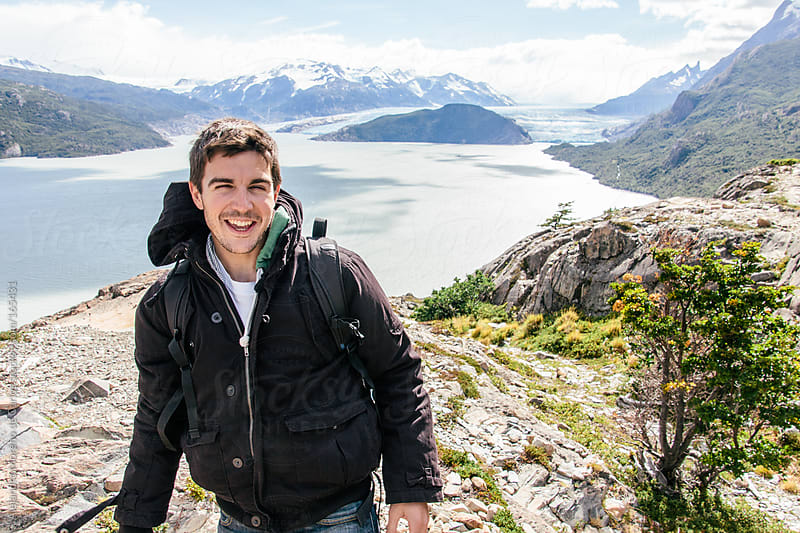 Young happy man portrait on glacier and mountain landscape in Patagonia by Alejandro Moreno de Carlos for Stocksy United