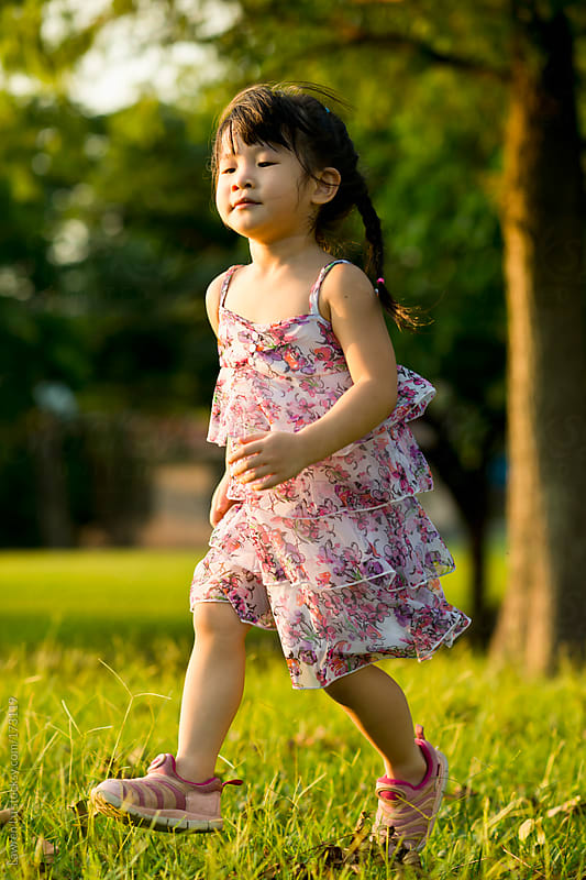 Little girl walking on the grassland by Lawren Lu for Stocksy United
