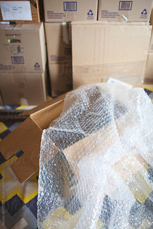 moving - packing up boxes with bubblewrap by Natalie JEFFCOTT for Stocksy United