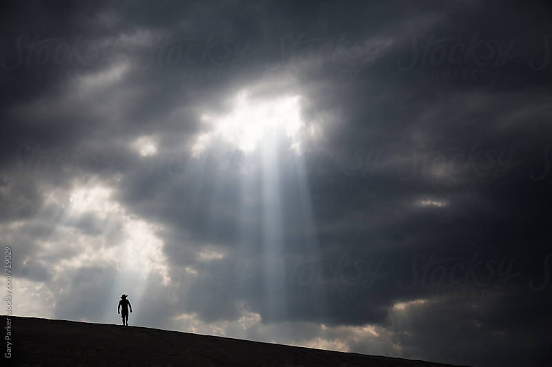A man walking across sand dunes as a ray of light shines through the clouds by Gary Parker for Stocksy United