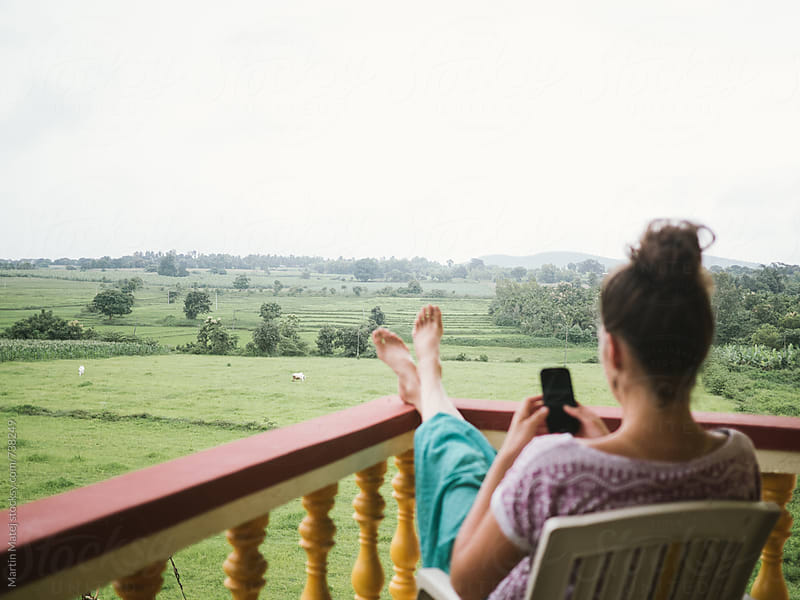 Girl with smartphone on the balcony by Martin Matej for Stocksy United