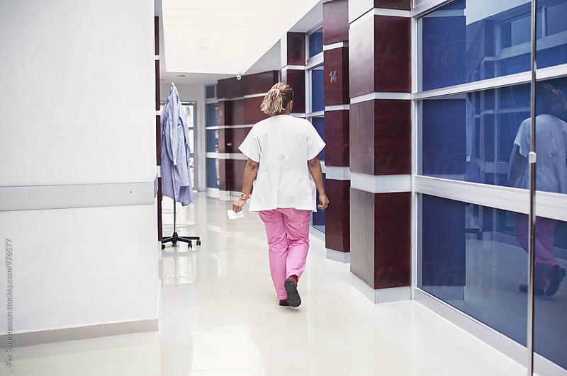 Female nurse walking down a hallway by Per Swantesson for Stocksy United