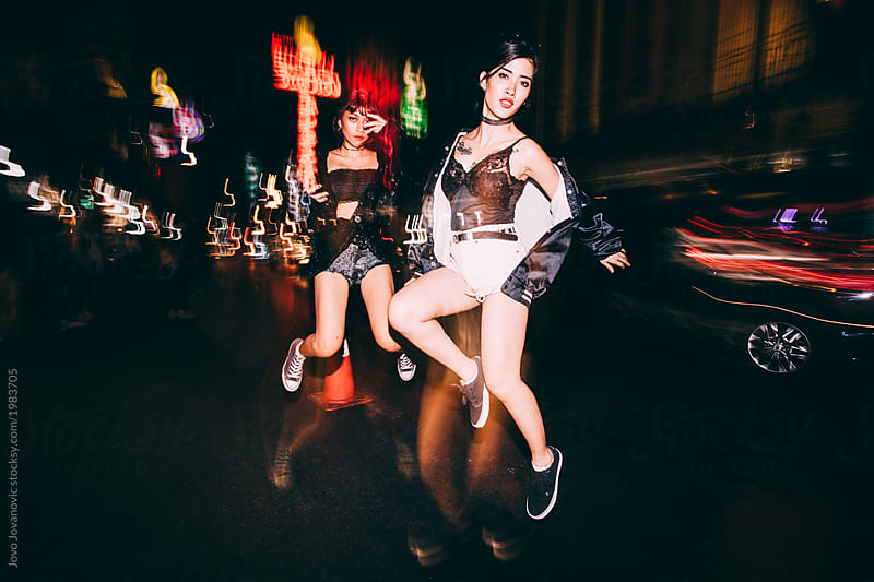 Two girlfriends jumping in  the city at night by Jovo Jovanovic for Stocksy United