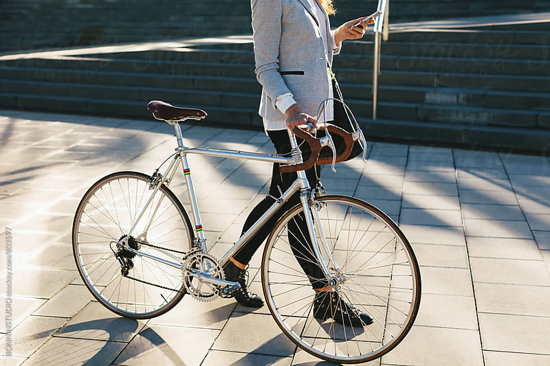 Closeup of a businesswoman walking with her vintage bicycle whilst using her phone outside. by BONNINSTUDIO for Stocksy United