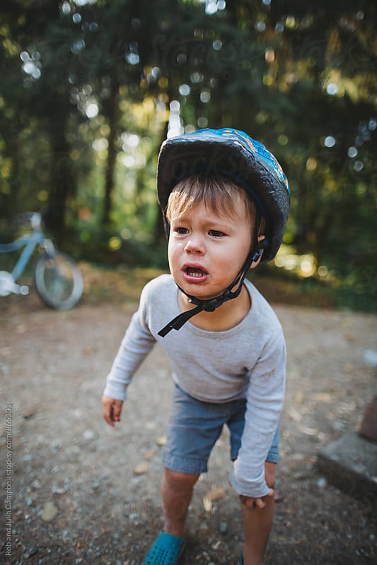 Upset toddler boy with helmet on  by Rob and Julia Campbell for Stocksy United