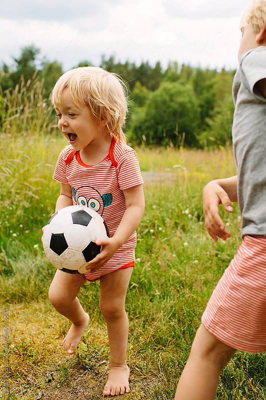 Little girl with bare feet plays ball with her brother by Julia Forsman for Stocksy United