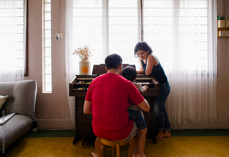 Family spending time together playing vintage piano by Alita Ong for Stocksy United