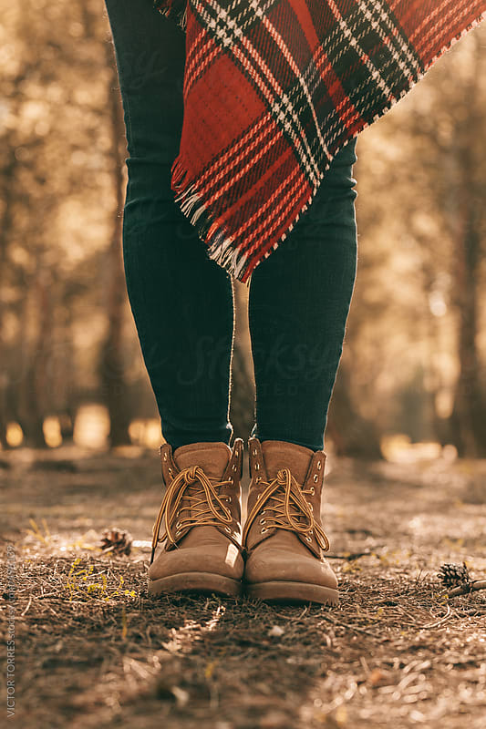 Woman Standing with Mountain Boots and Red Blanket by VICTOR TORRES for Stocksy United