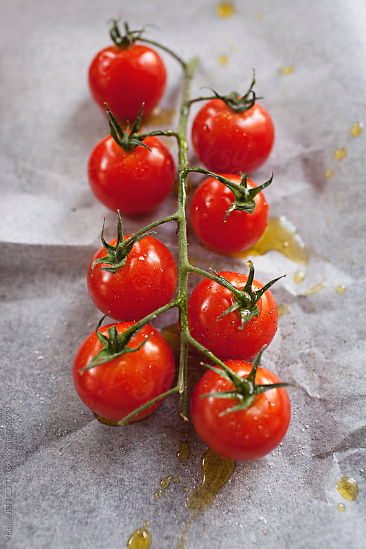 fresh cherry tomatoes on a vine with oil and salt on baking paper by Natalie JEFFCOTT for Stocksy United