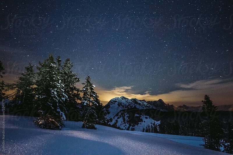 snowcovered austrian mountains under starry night by Leander Nardin for Stocksy United