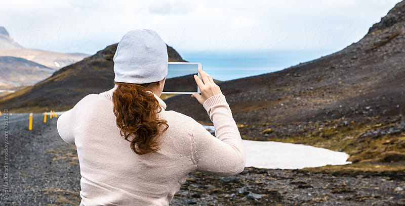 woman photographing the landscape of Iceland by Andreas Gradin for Stocksy United