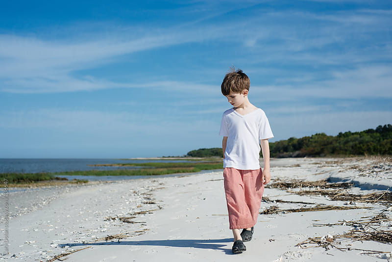 Boy explores a beach in summer by Cara Dolan for Stocksy United