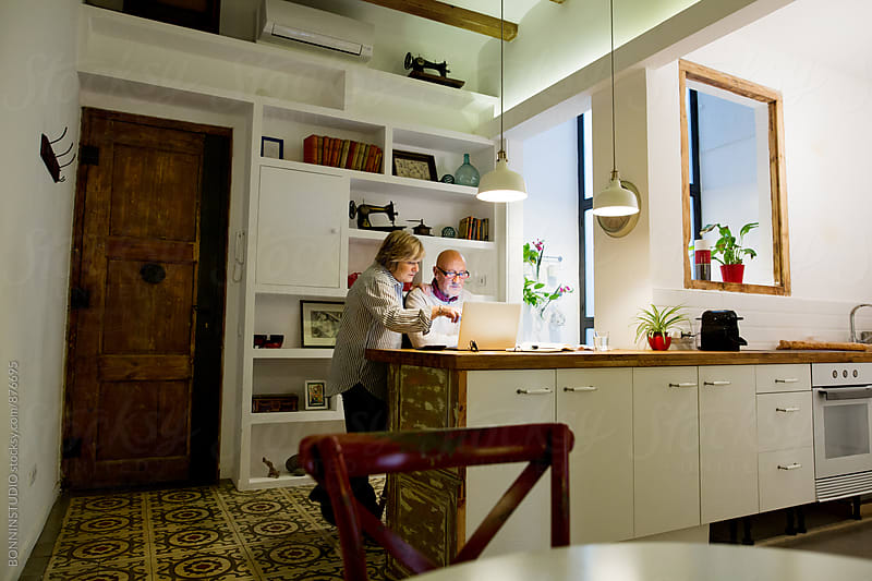 Elderly couple managing household expenses at evening. by BONNINSTUDIO for Stocksy United