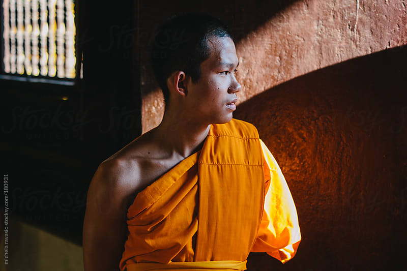 Portrait of young Buddhist monk leaning against the door of the temple by michela ravasio for Stocksy United