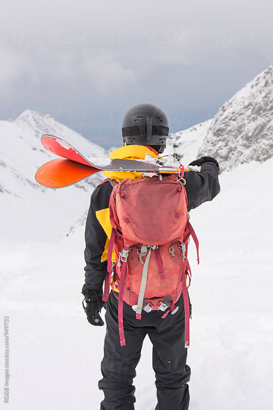 Skier holding his skis looking at the mountains by RG&B Images for Stocksy United
