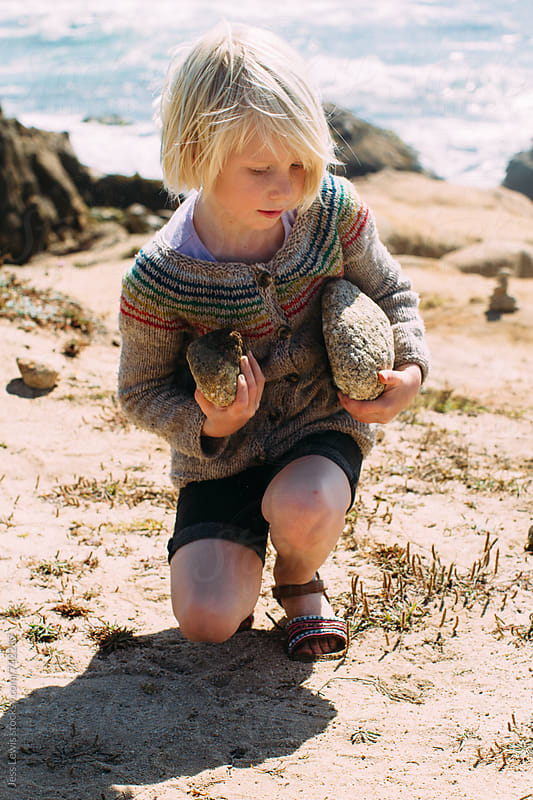 child carrying rocks on beach by Jess Lewis for Stocksy United