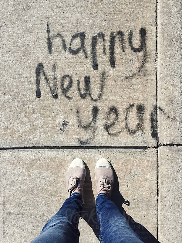Looking down on woman's feet with Happy New Year written on sidewalk by Jacqui Miller for Stocksy United
