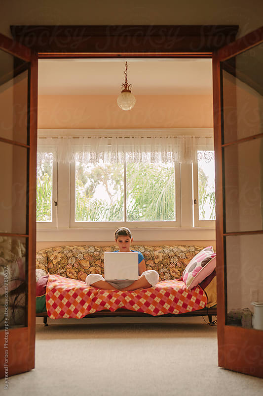 Teen Girl on Laptop at Home by Raymond Forbes LLC for Stocksy United